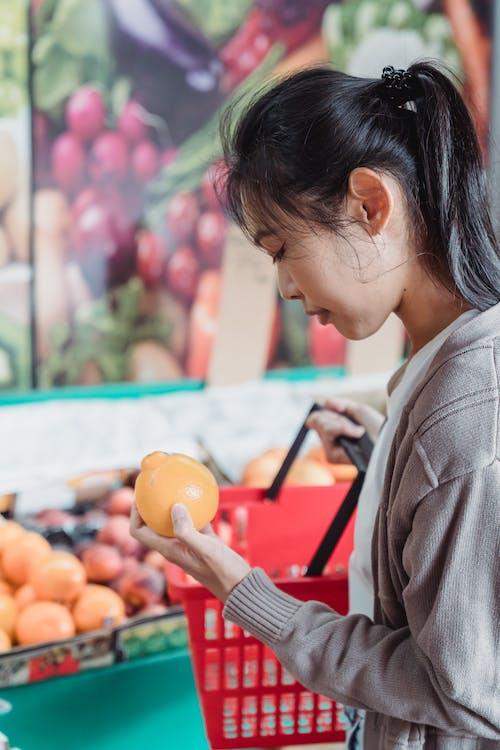 Woman in Gray Jacket Holding Orange Fruit