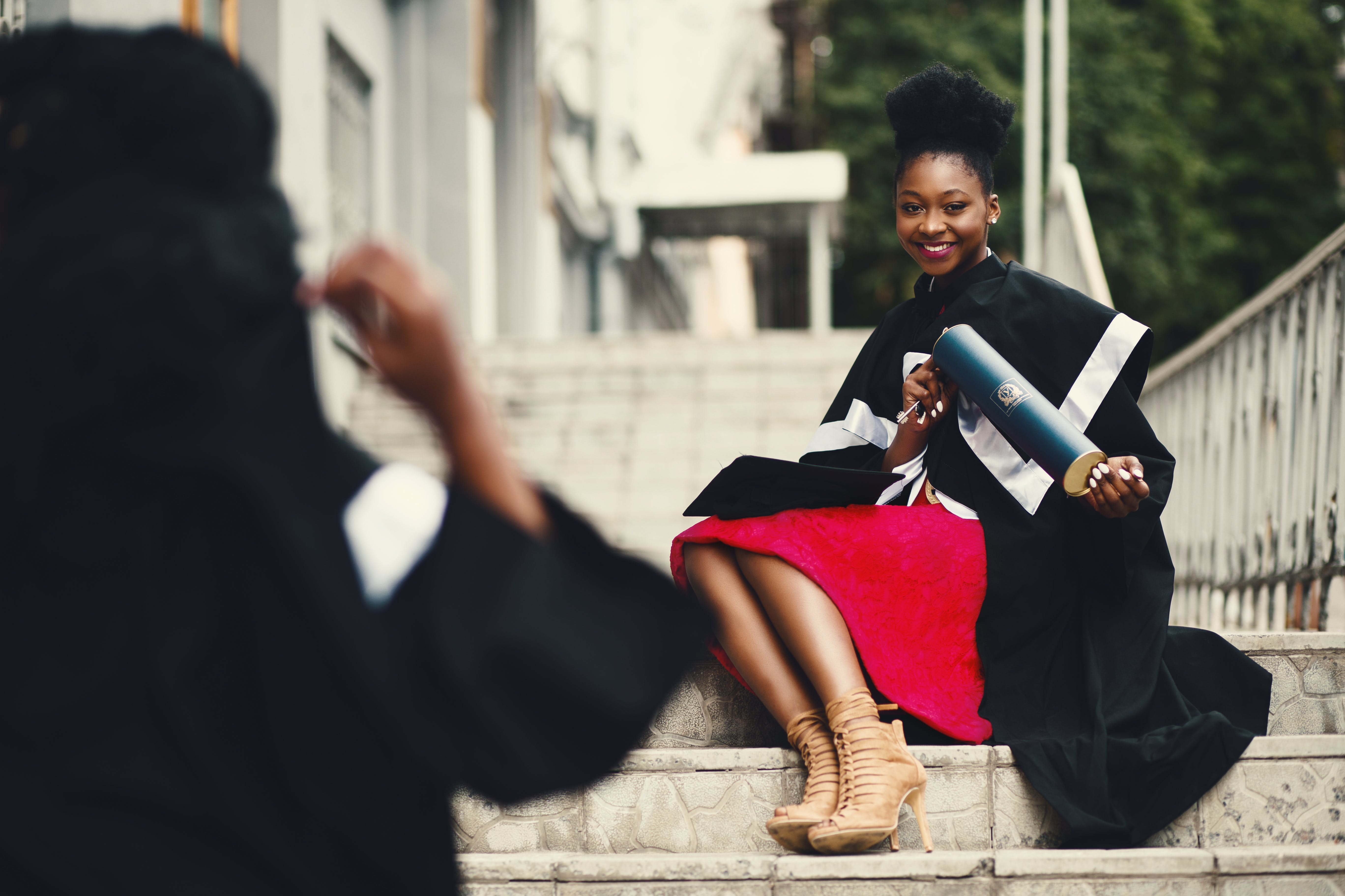 Woman Wearing Black Graduation Coat Sits on Stairs