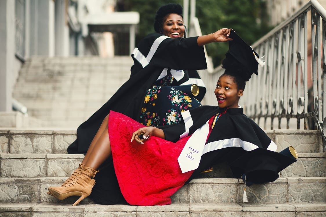 Shallow Focus Photography of Two Women in Academic Dress on Flight of Stairs