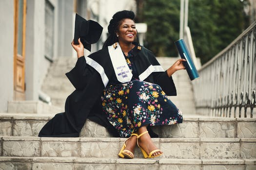 Photo of Woman Wearing Academic Dress and Floral Dress Sitting on Stairway