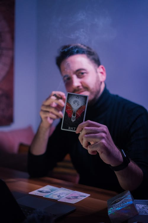 Male fortune teller showing tarot card and looking at camera while sitting at table in semi dark room
