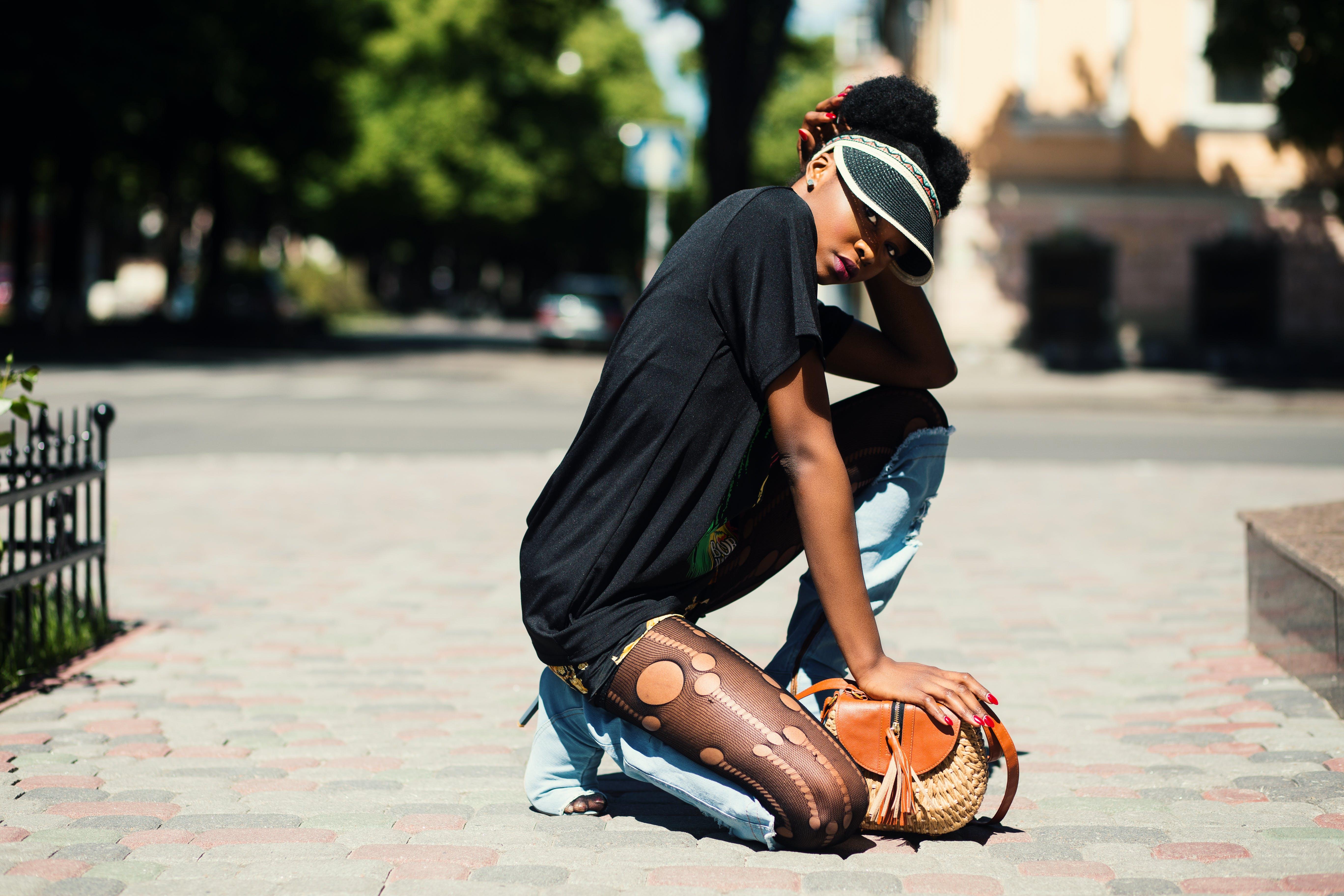 Woman Wearing Black T-shirt Kneeling on Ground