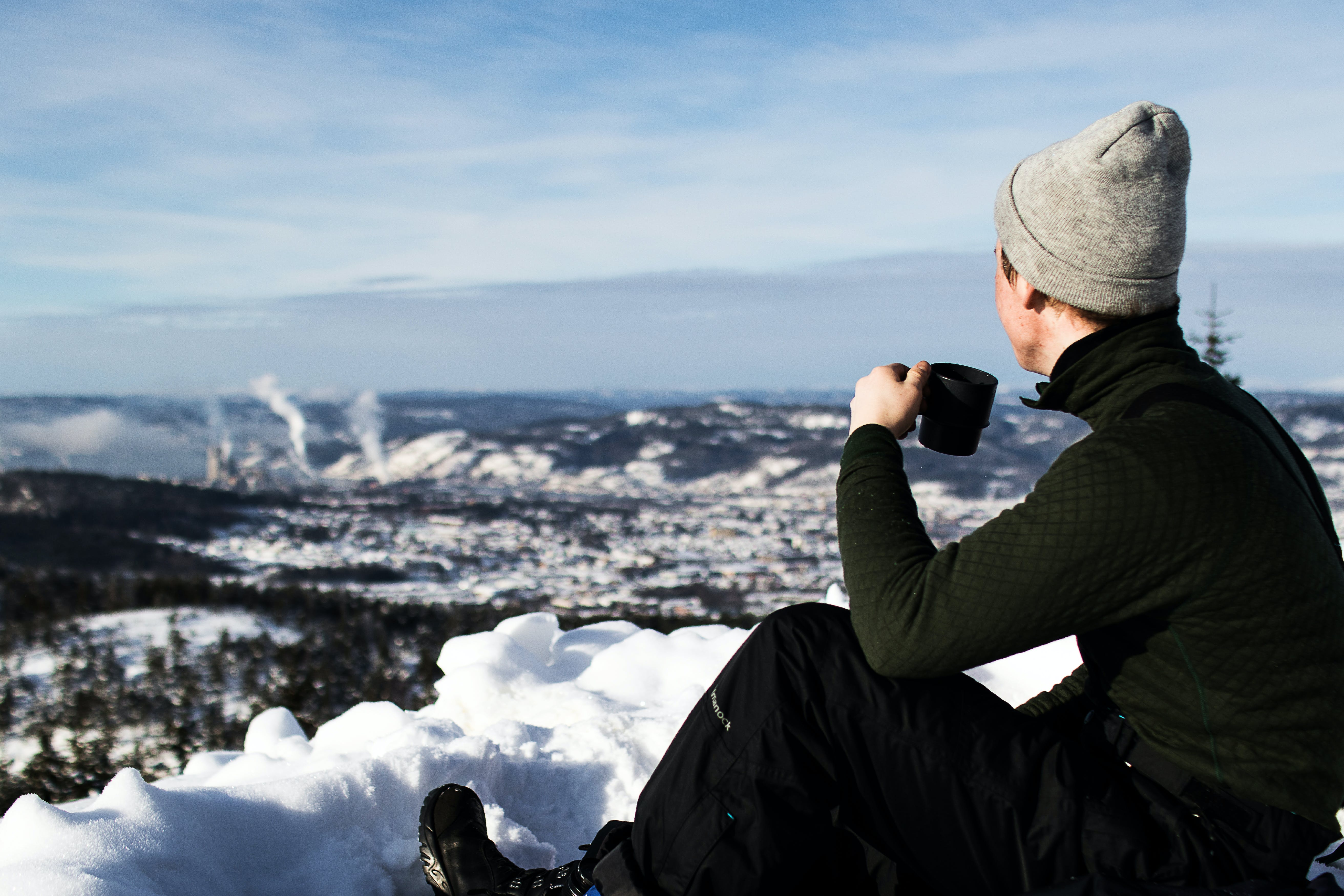 Man Wearing Jacket and Holding Cup Sitting on the Snow