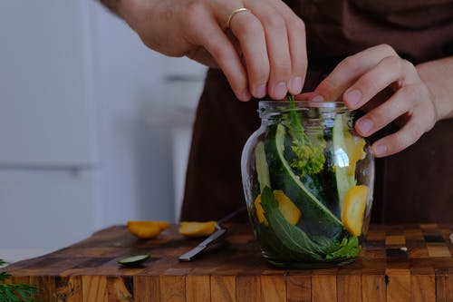 A Person Putting Vegetables into the Glass Jar
