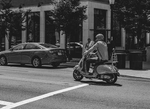 Grayscale Photo of a Man Riding a Motorcycle on the Road