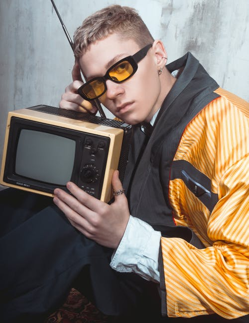 Man in Sunglasses Holding a Vintage Television