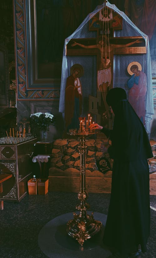 Nun in Black Robe Standing in Front of the Crucifixion