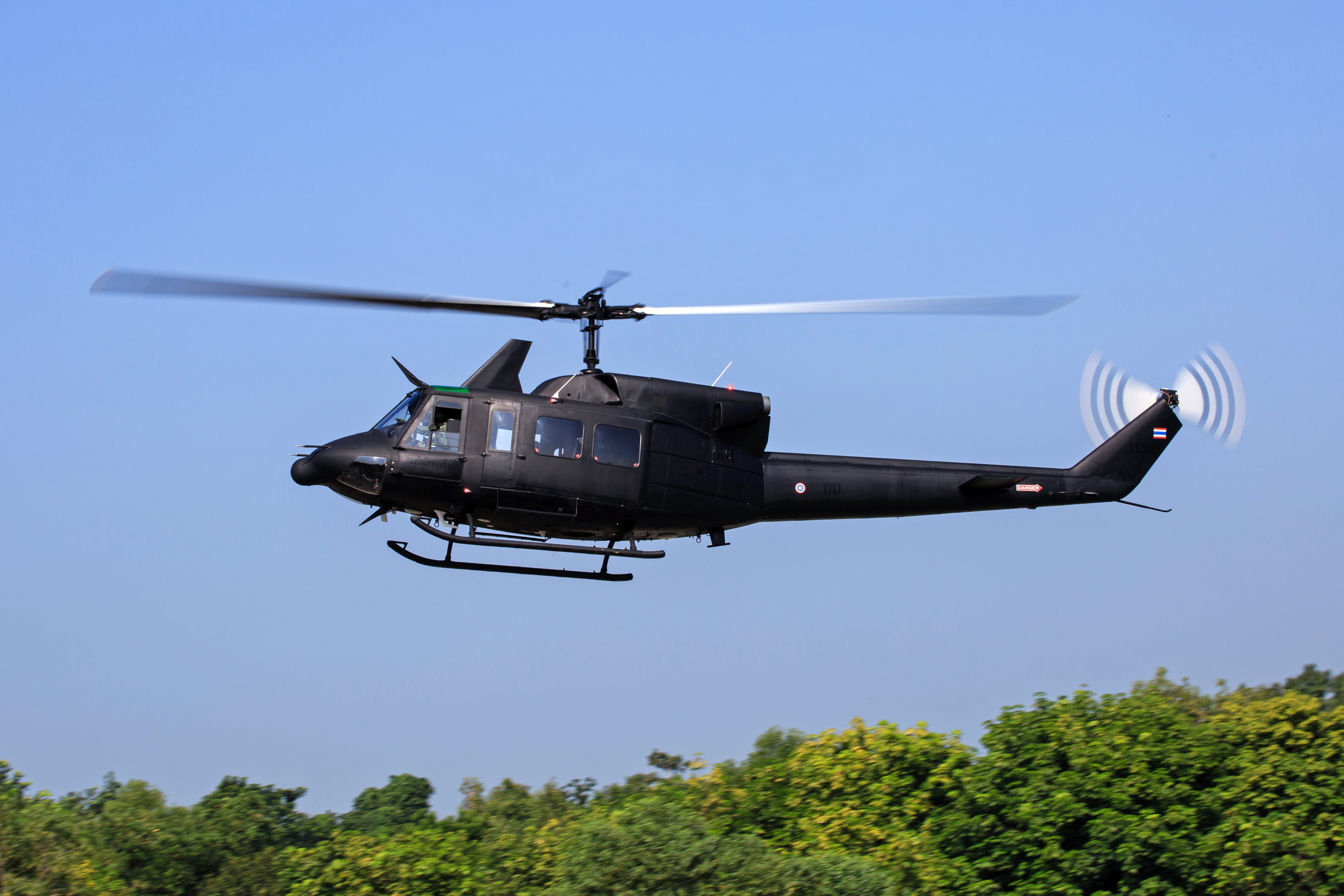 Black Helicopter Flying Above Green Trees