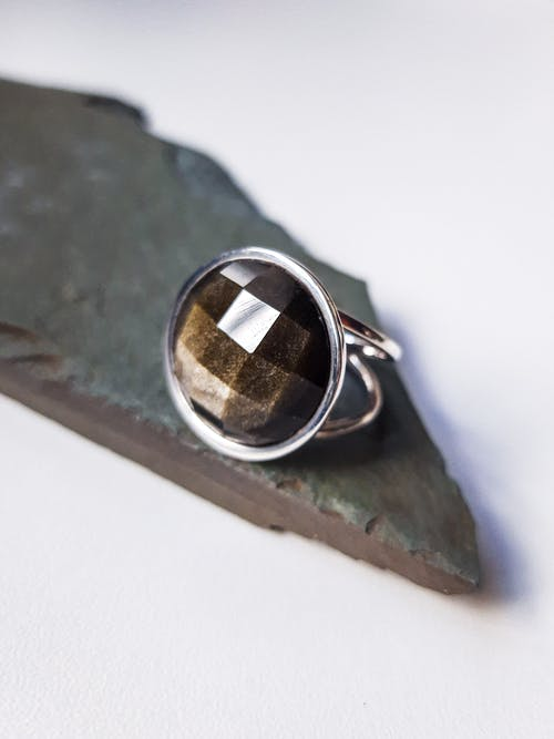 From above of creative design of silver ring with semiprecious stone on rock piece on light background