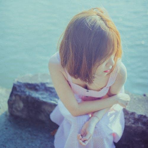 Girl in White Dress Sitting on White Rock Near Body of Water