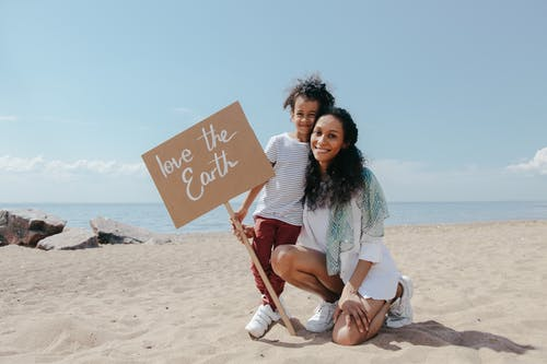 A Mother and Her Child Holding a Signage on The Beach