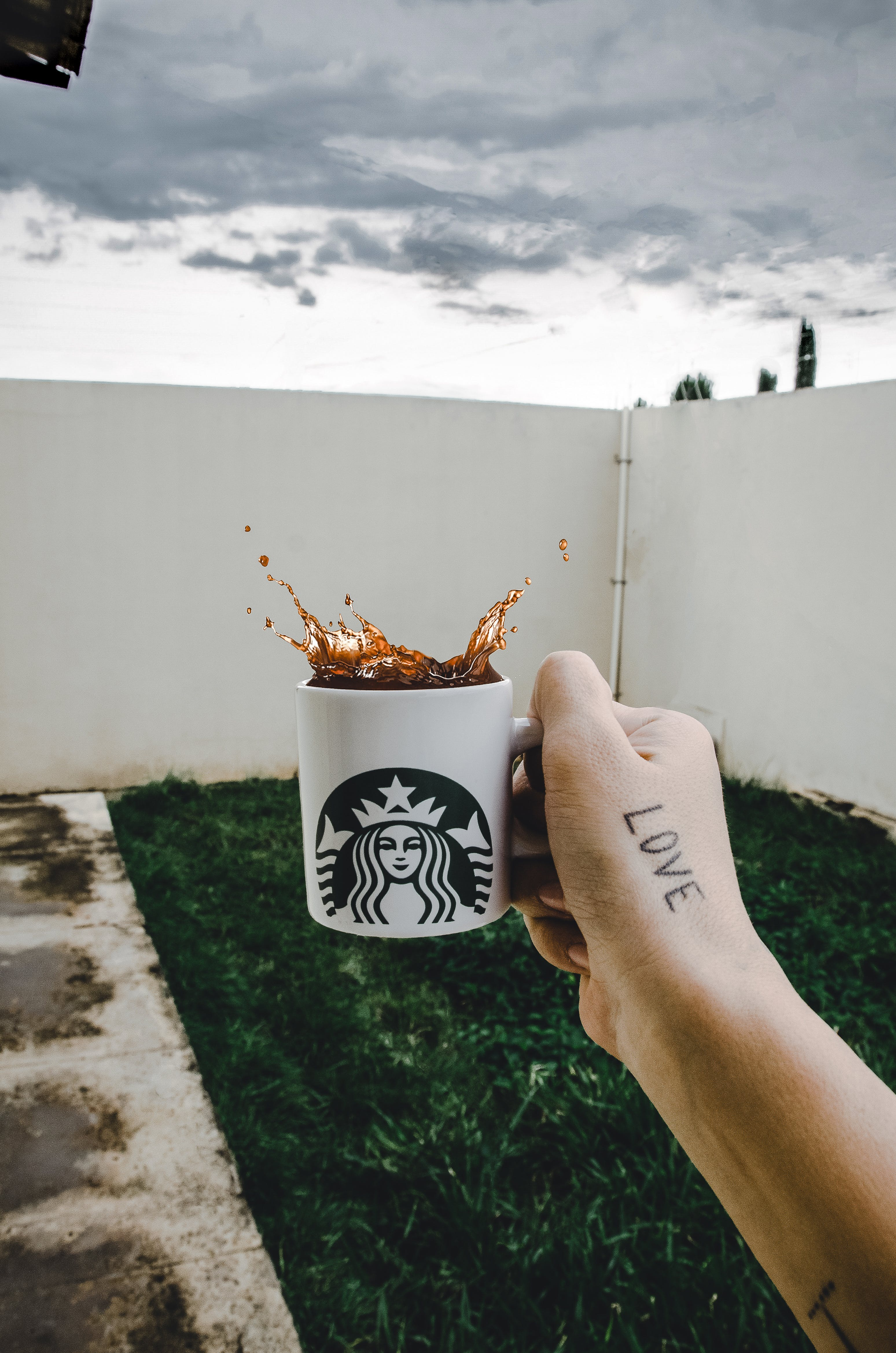Person Holding Starbucks Cup With Brown Beverage