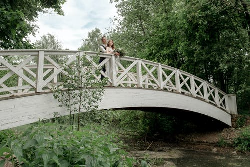 Woman in White Shirt and Black Pants Standing on White Bridge