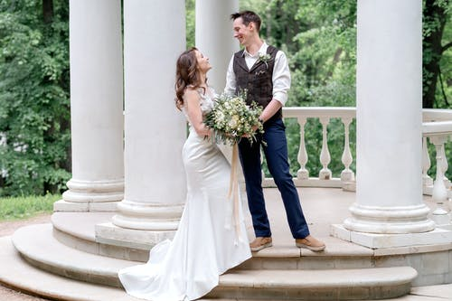 Man in Blue Suit and Woman in White Wedding Dress Holding Bouquet of Flowers