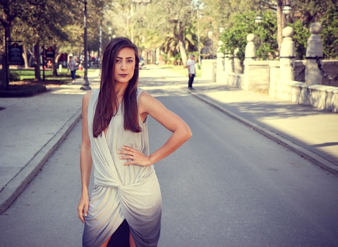 Woman Weairng White and Gray Sleeveless Dress Standing on Gray Road