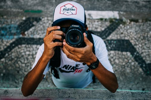 Man Wearing White Nike Sb Shirt Holding Black Dslr Camera