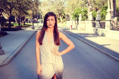 Woman in Gray Sleeveless Mini Dress Standing on Pavements