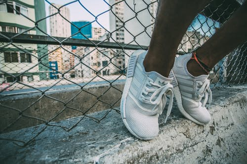 Person Wearing White Adidas Low Top Shoe Near Gray Cyclone Fence