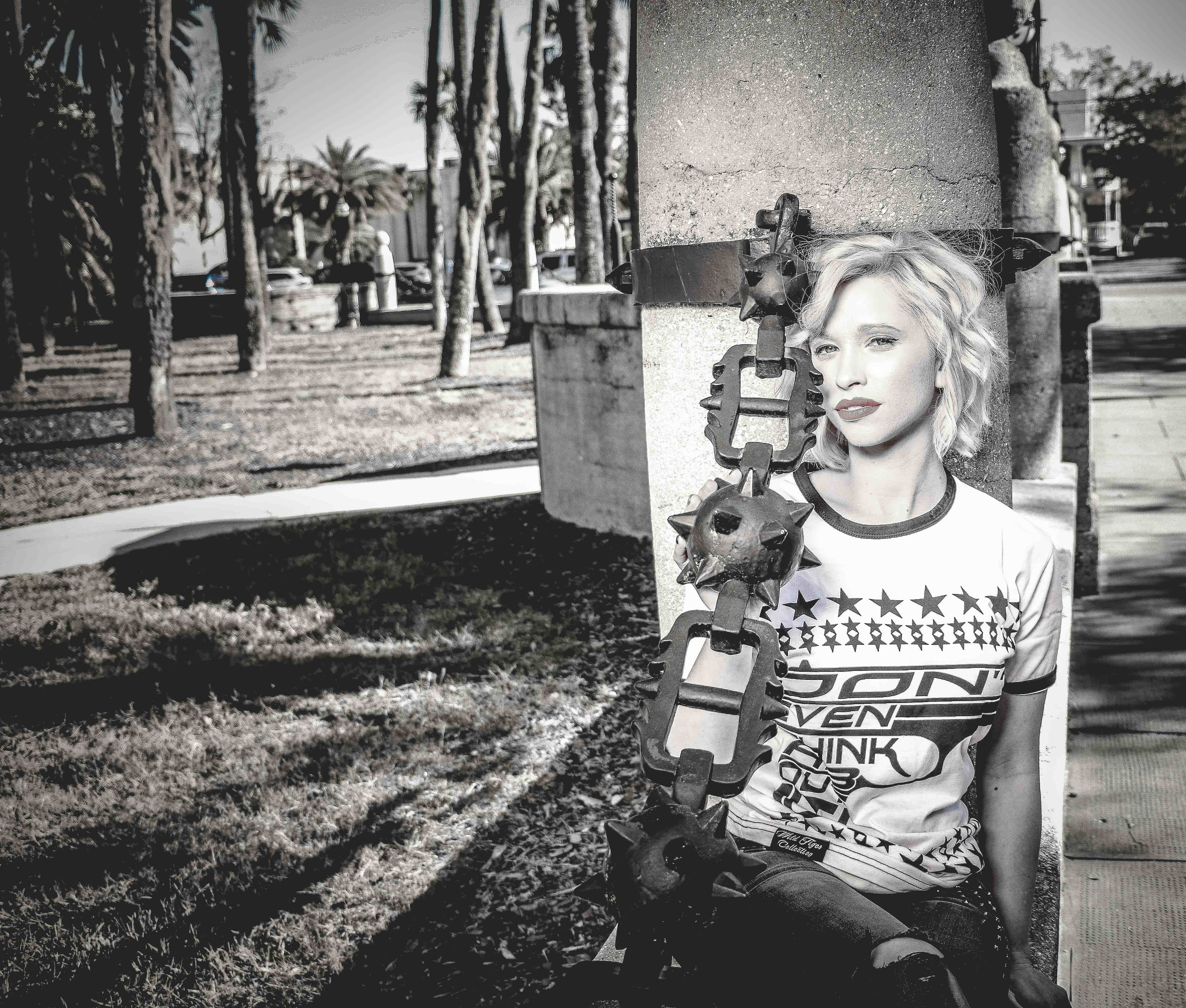 Woman Sitting Beside Gray Concrete Post Grayscale Photo