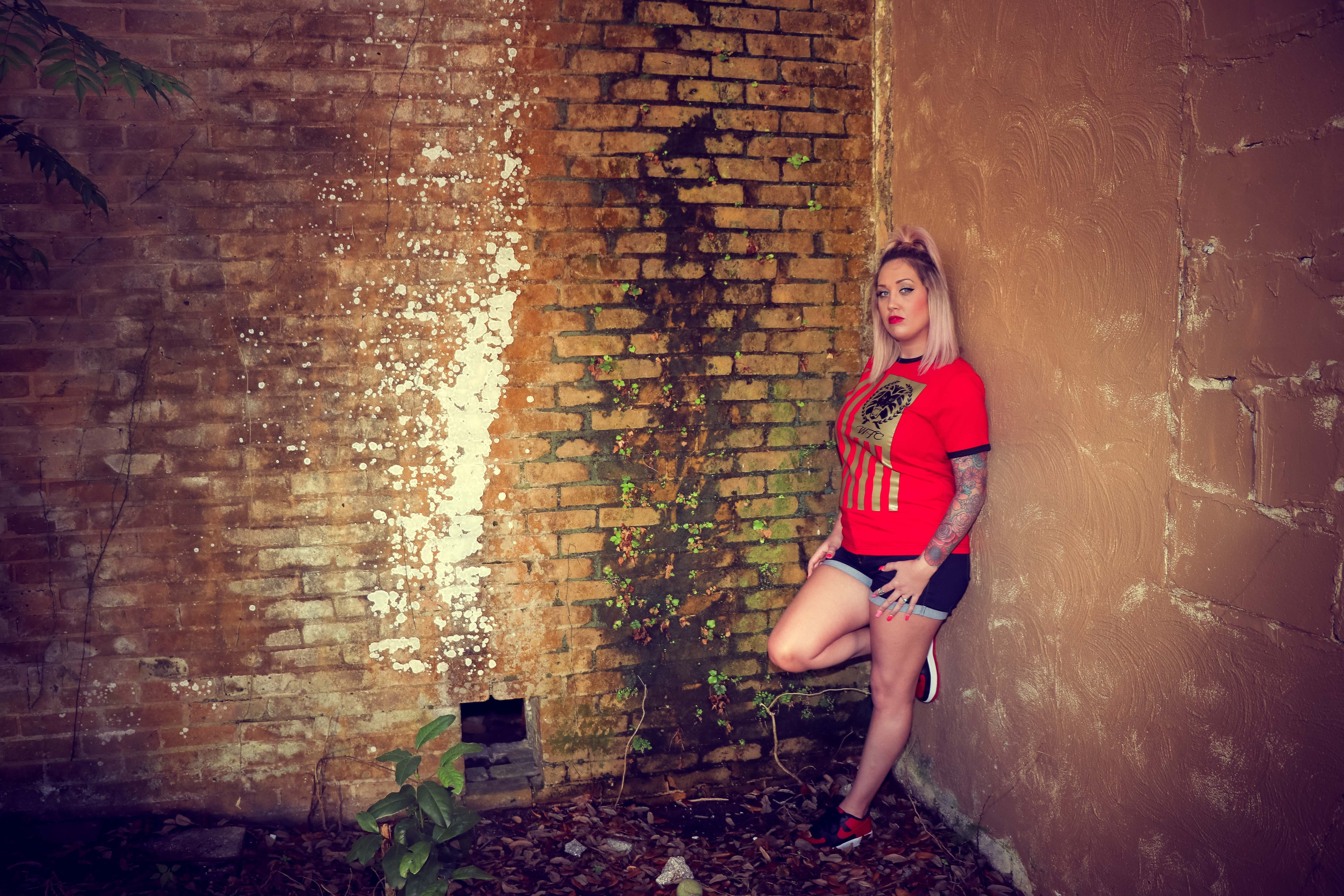 Woman Wearing Red Crew-neck Sleeved Shirt and Blue Denim Short Shorts