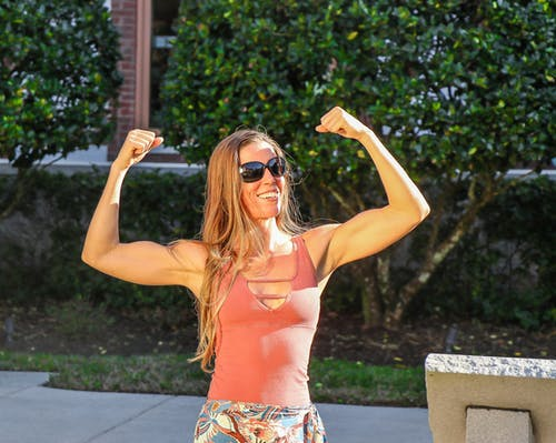 Woman in Pink Tank Top Showing Her Biceps