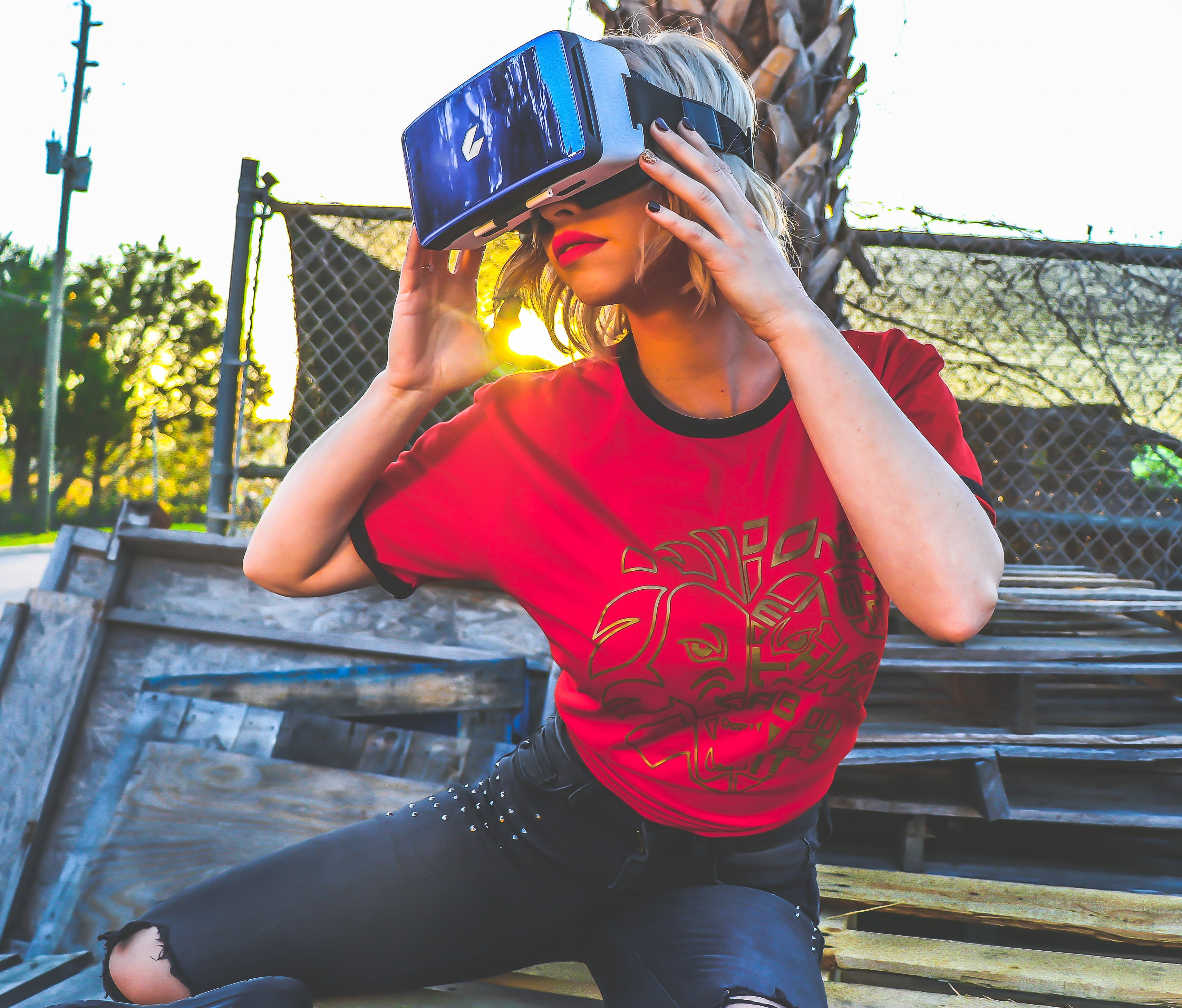 Woman Wearing Red and Black Top and Blue Distressed Bottoms Wearing Gray and Black Virtual Reality Sunglasses