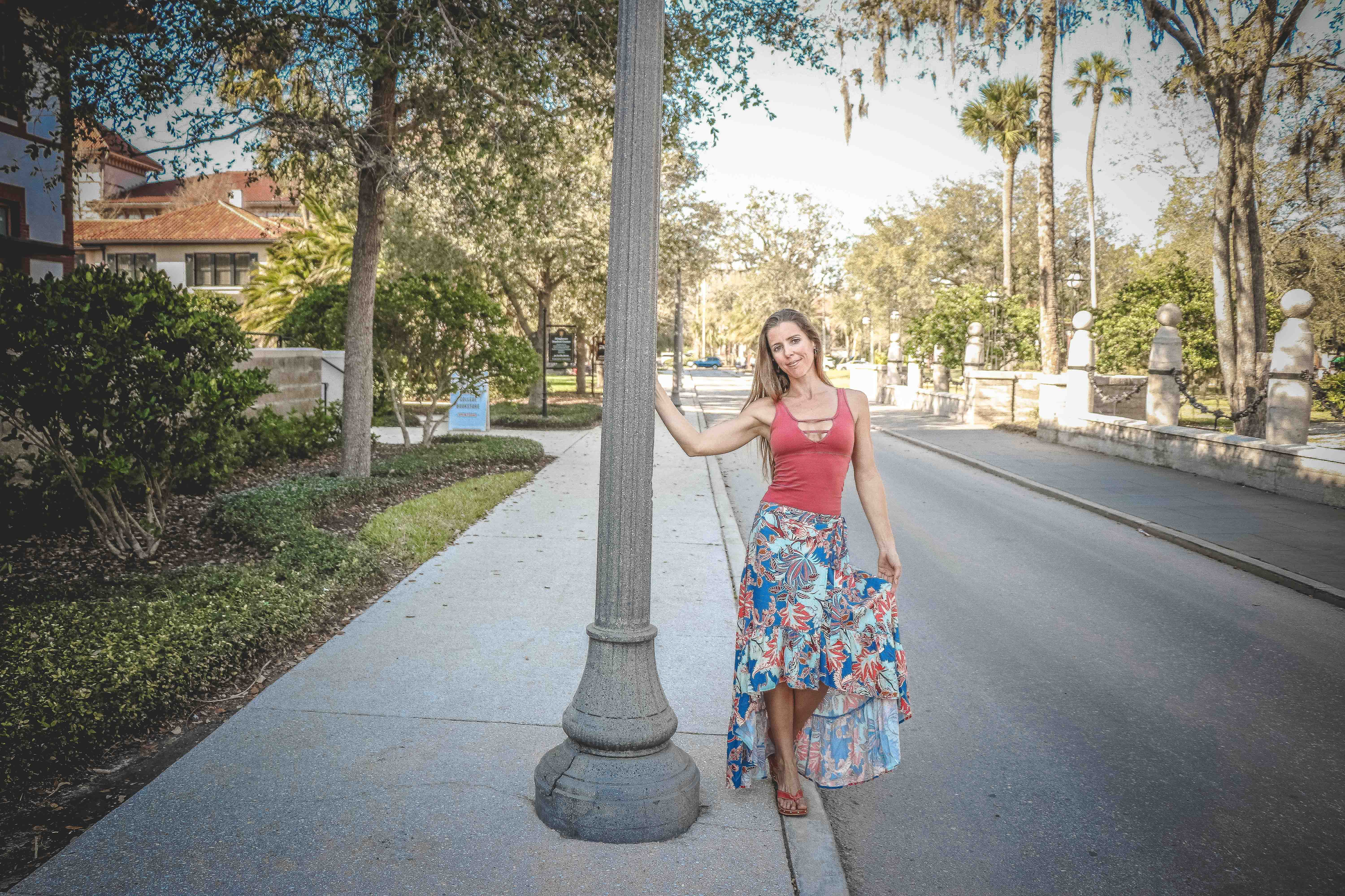 Woman Wearing Red and Blue Floral Tank Dress Beside Concrete Road