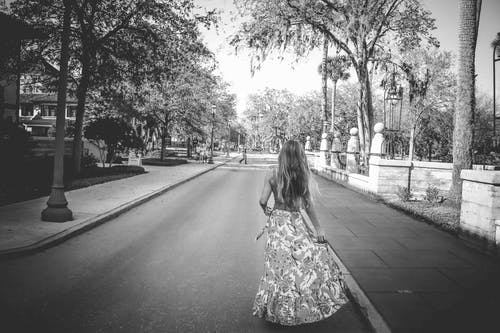 Woman in Floral Dress Standing on Road