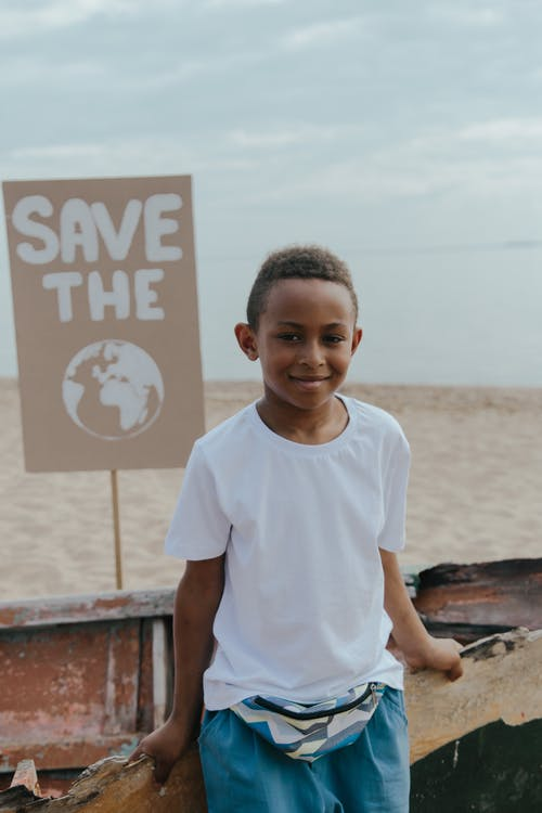 A Boy in White Shirt Standing In Front of a Save The Earth Signage