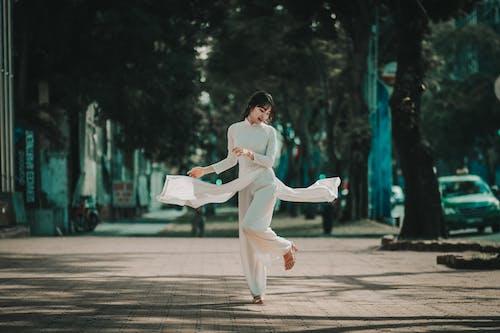 Woman in White Dress Walking on Sidewalk