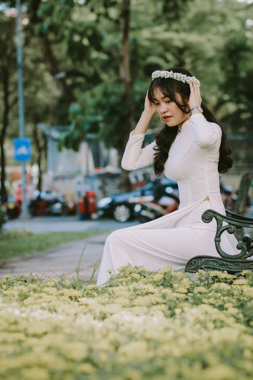 Woman in White Long Sleeve Dress Sitting on Green Grass