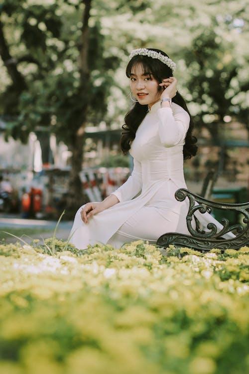 Woman in White Long Sleeve Dress Sitting on Black Metal Bench