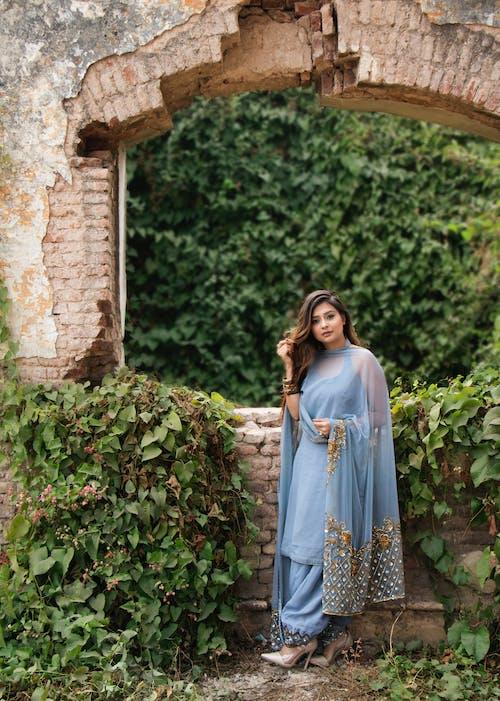 Frau Im Blauen Kleid, Das Nahe Braunen Betonsteinen Steht