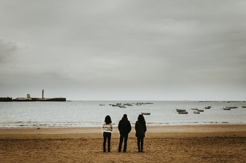 Three Person Standing Near the Seashore