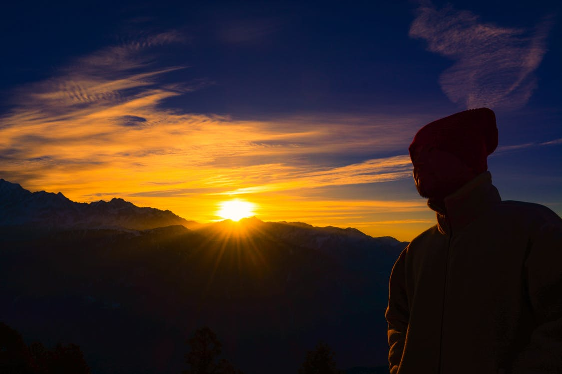 Silhouette of Person Near Mountain during Golden Hour