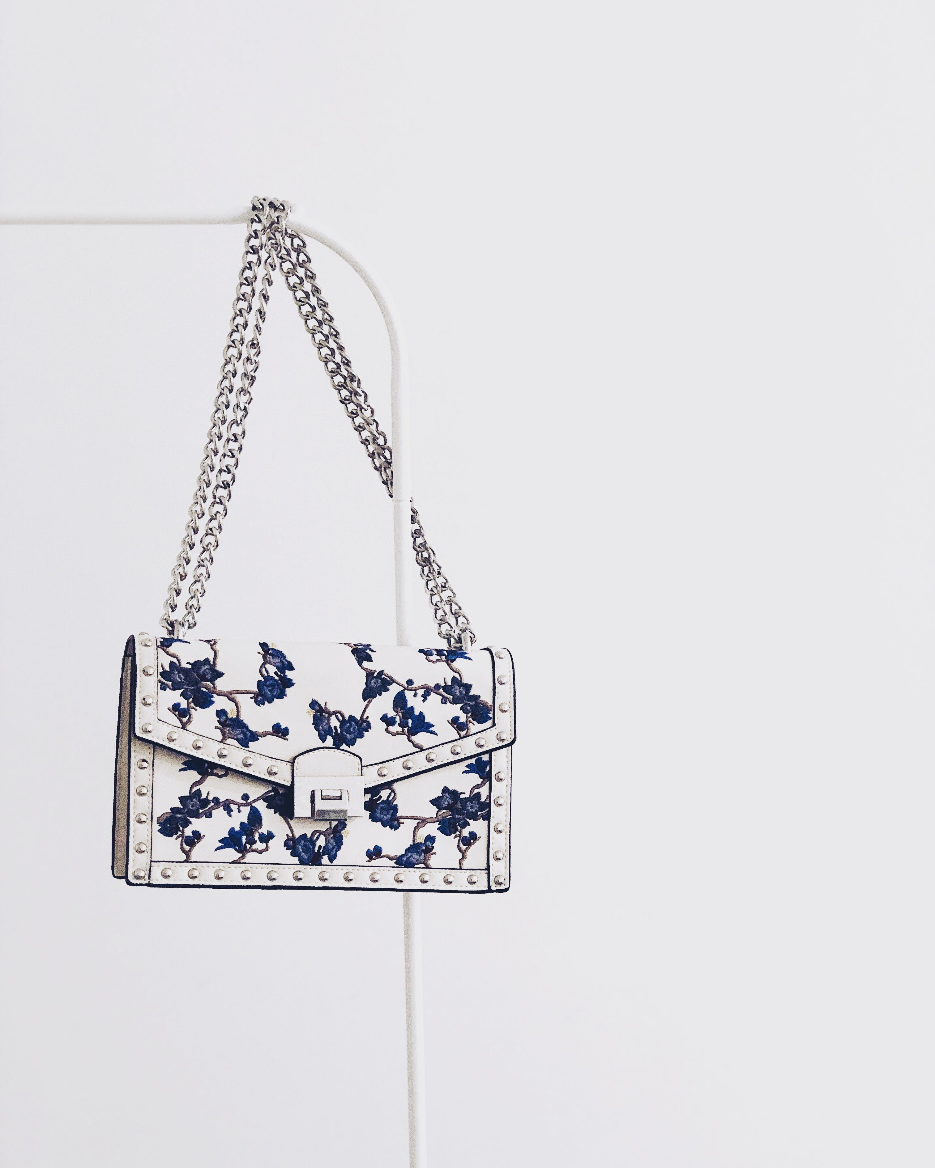 White and Blue Floral Flap Sling Bag Hanging on White Steel Rack