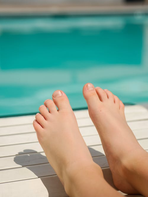 Person's Feet on White Wooden Surface