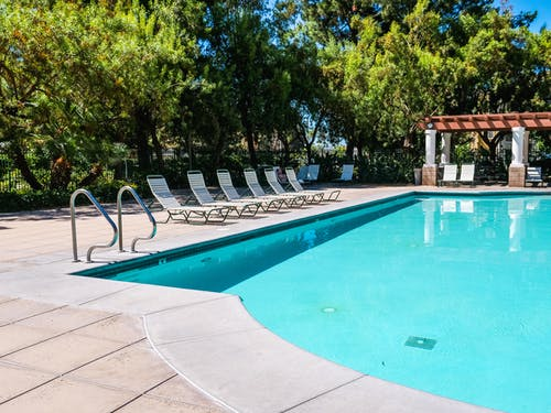 Swimming Pool Near Green Trees With Outdoor Lounge Chairs