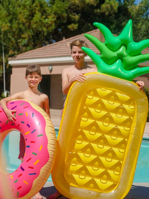 Boys Standing On Poolside With Yellow Inflatable Bed And Pink Swim Ring