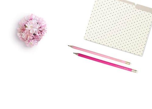 Pink Petaled Flower Beside Two Pink Pens