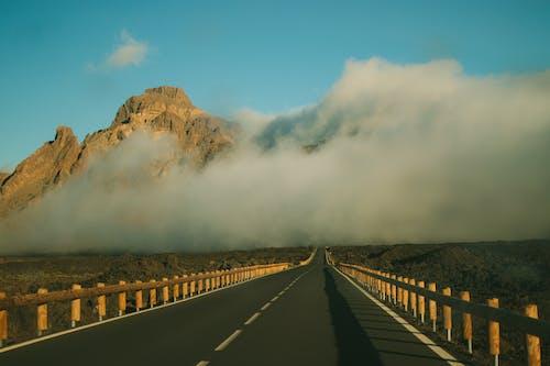 Black Asphalt Road Near Brown Mountain Under White Clouds