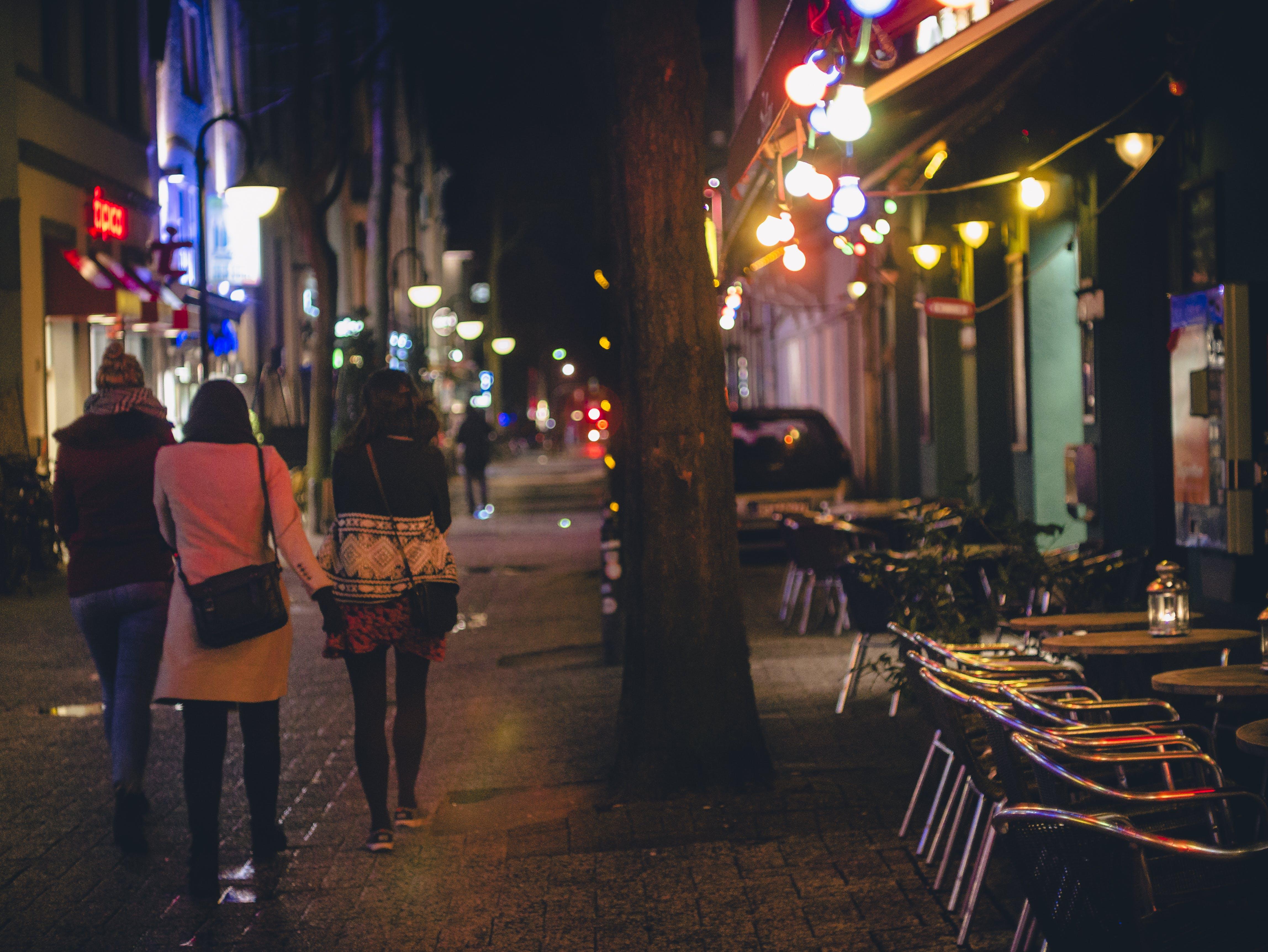 Three Women Walking during Nightime