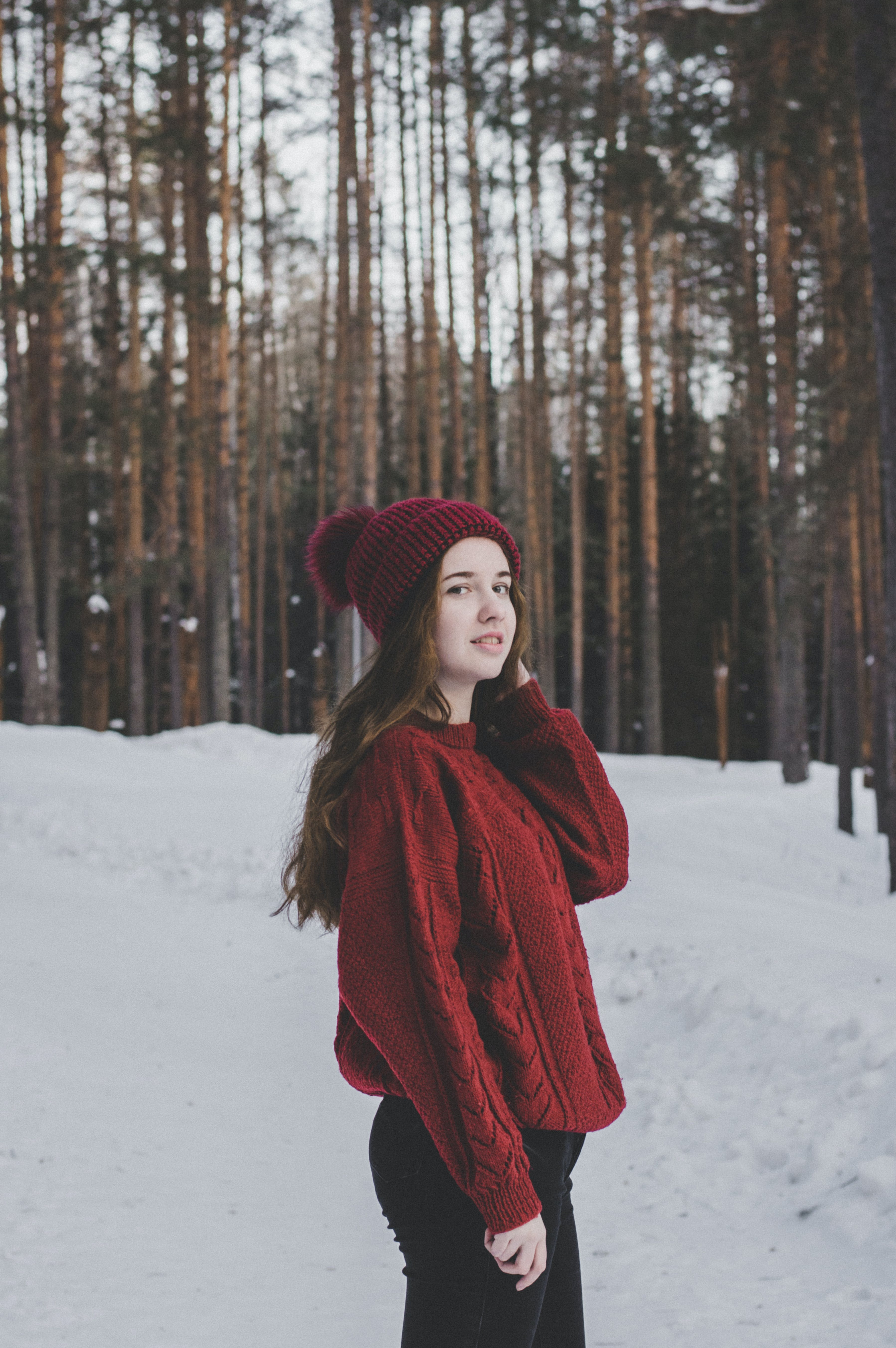 Woman Wearing Red Sweater and Red Beanie Under Forest
