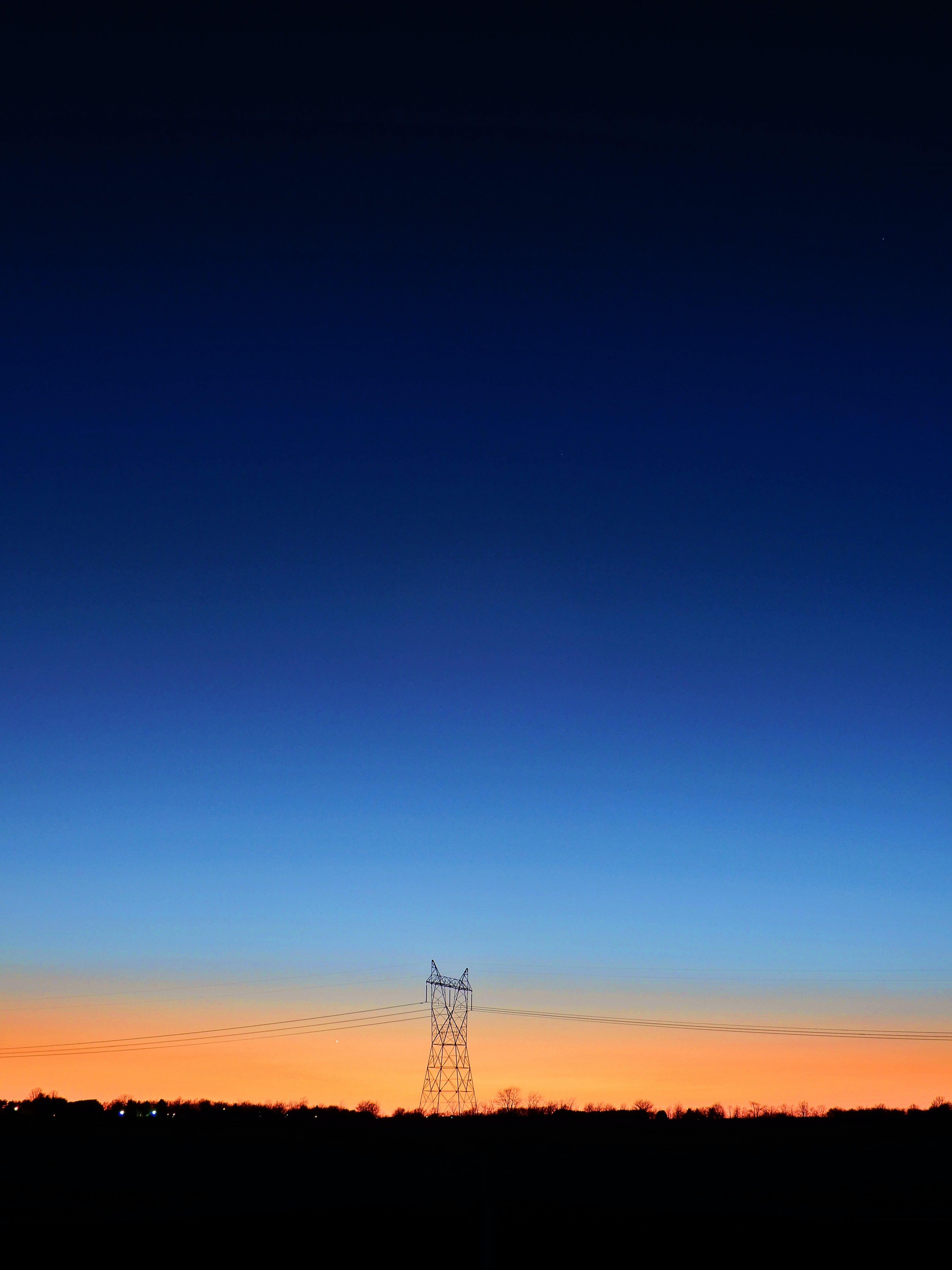 Black Transmitter Tower Under Blue and Orange Sky