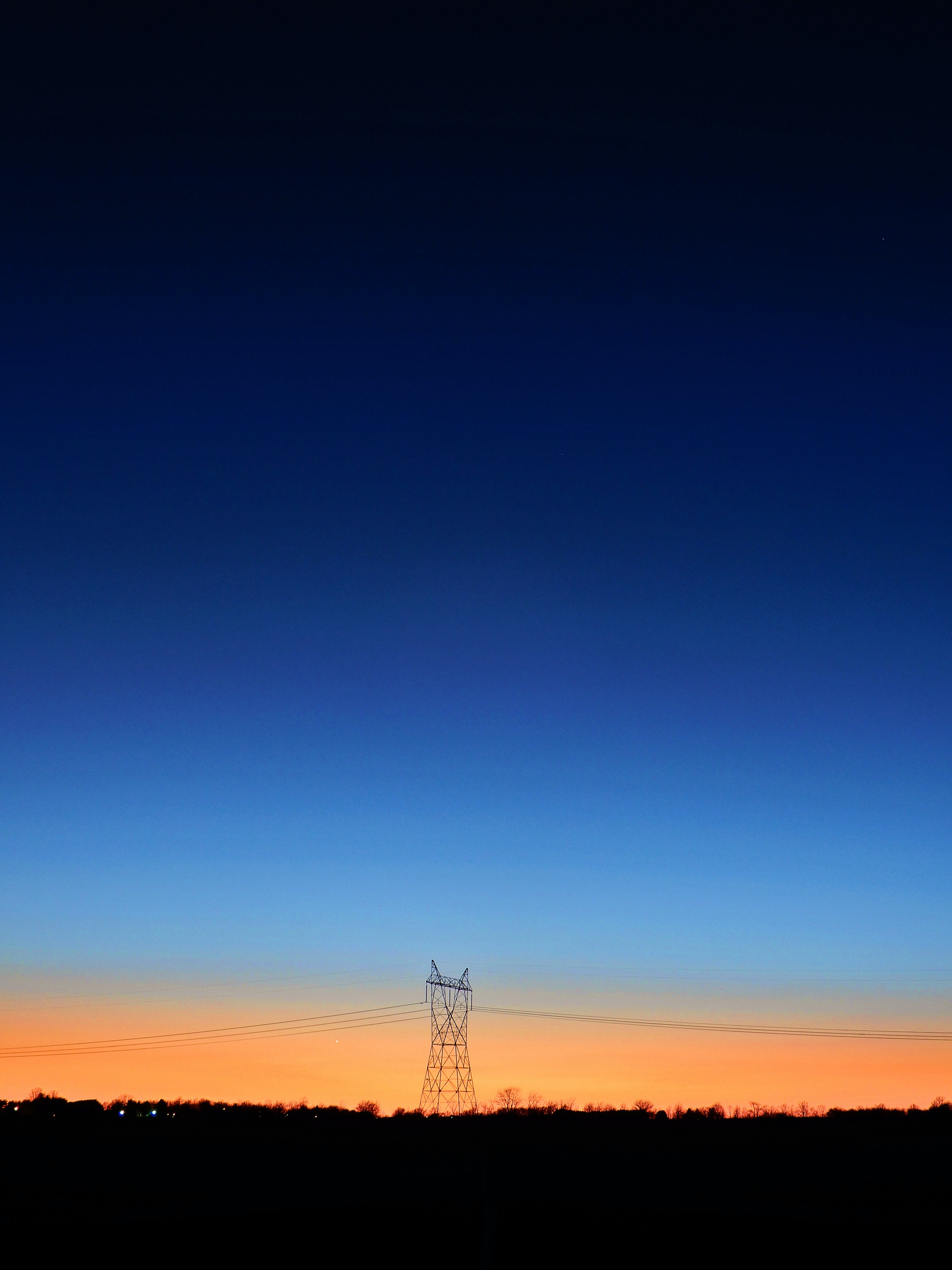 Black Transmitter Tower Under Blue and Orange Sky