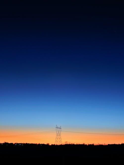 파란색과 주황색 하늘 아래 검은 색 송신기 타워