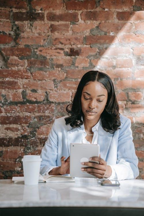 Woman in Light Blue Blazer using Tablet
