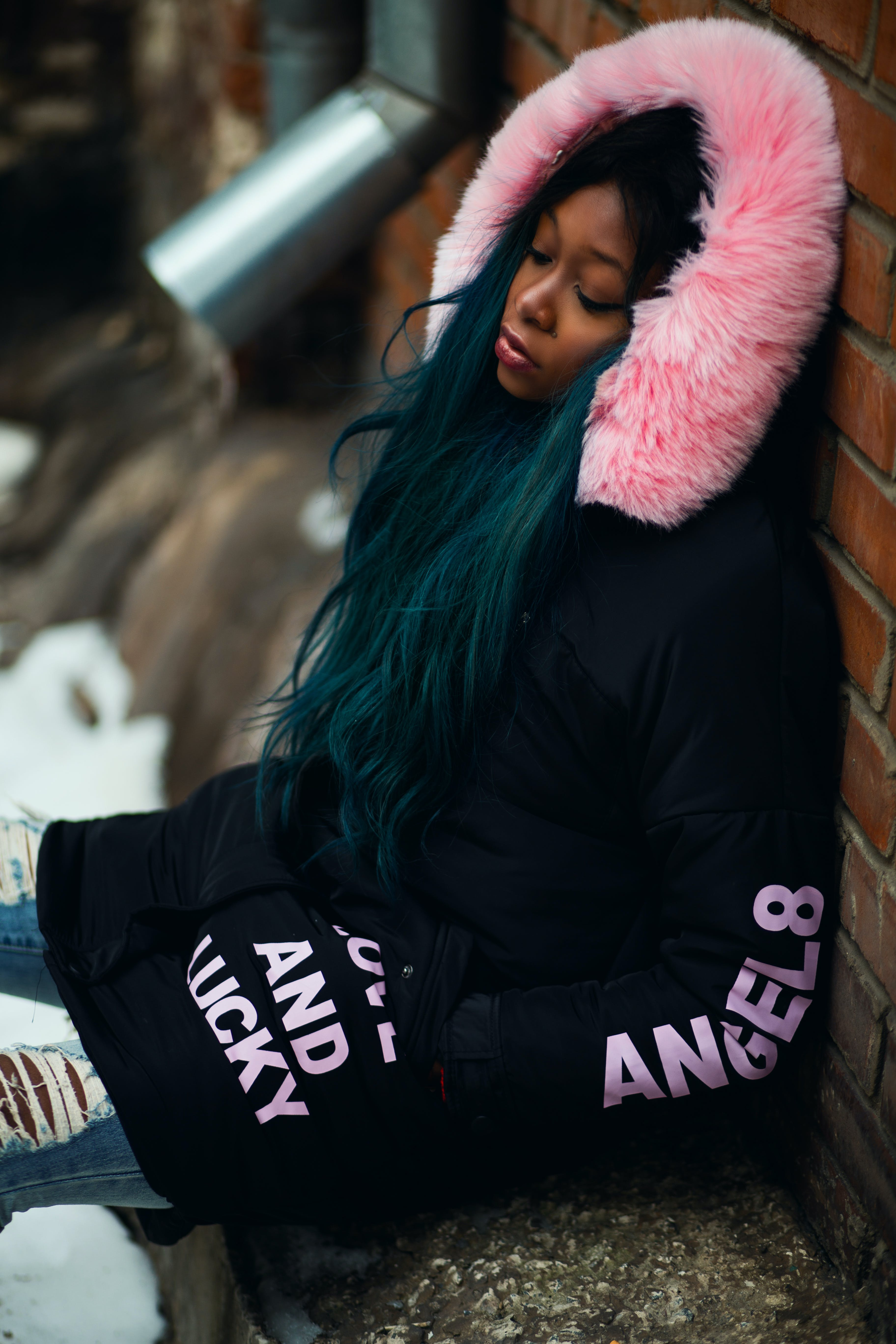 Woman Wearing Black and Pink Coat Leaning on Wall