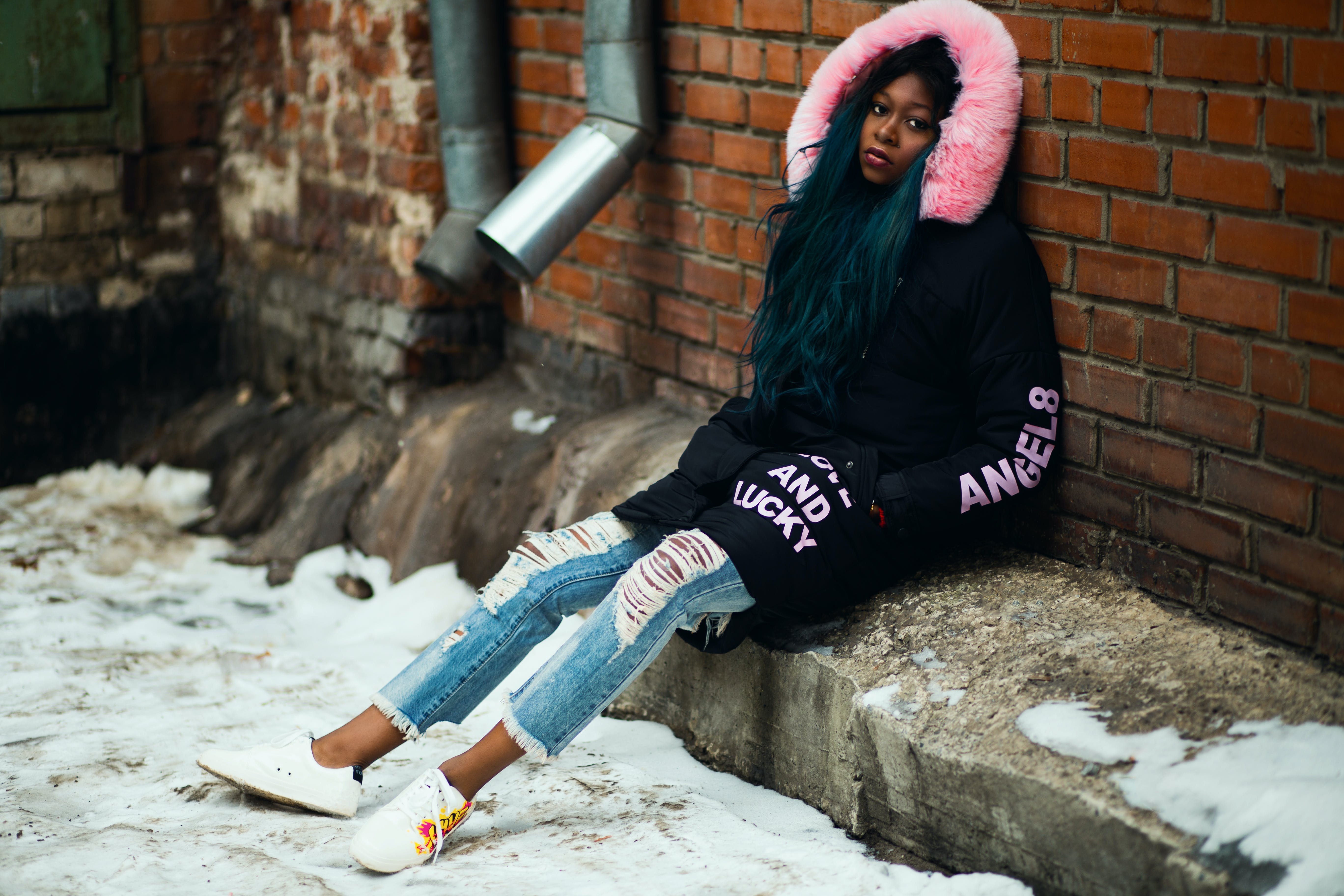 Woman Wearing Black and Pink Parka Leaning on Brown Brick Wall