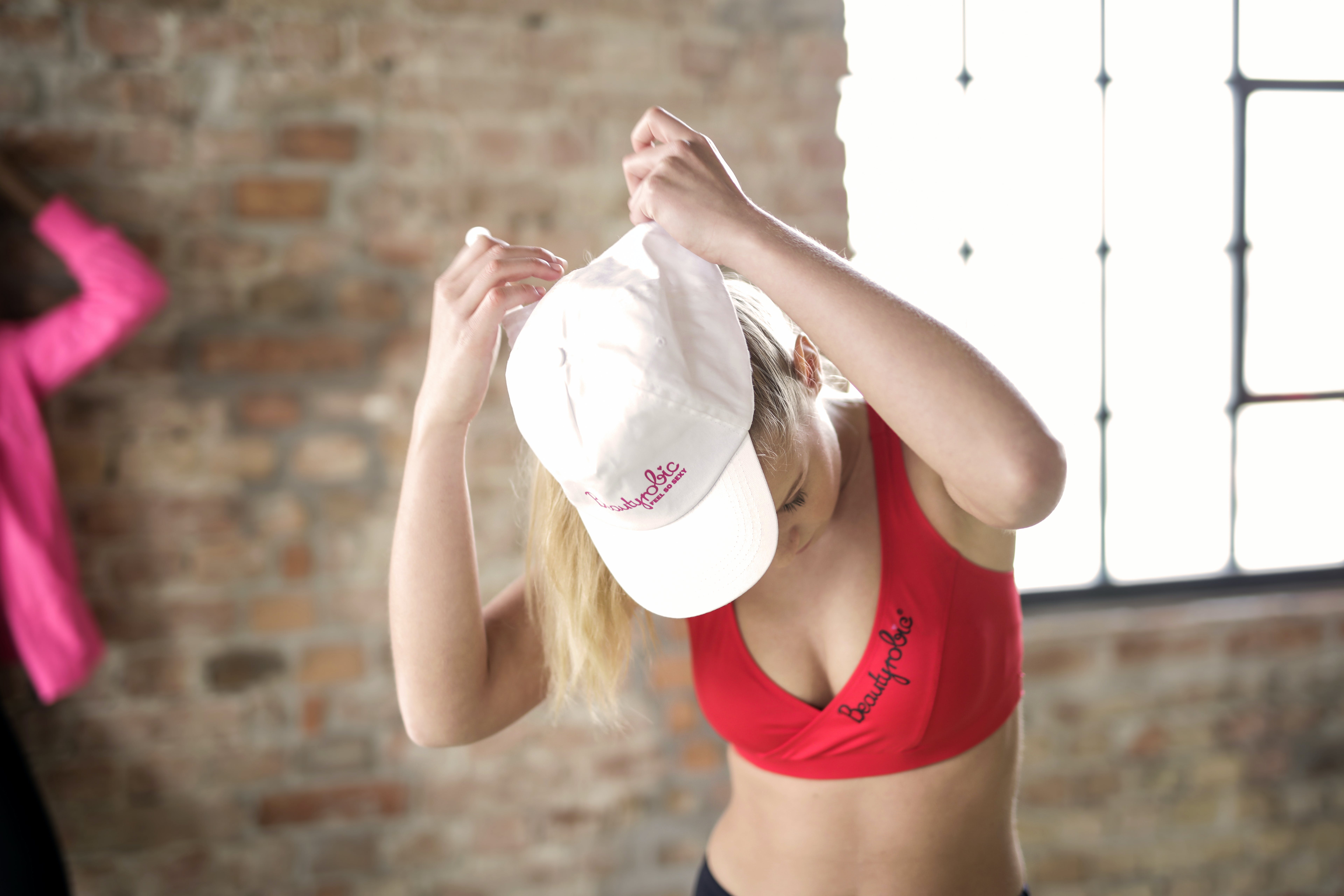 Woman Wearing Red Crop Top and White Cap